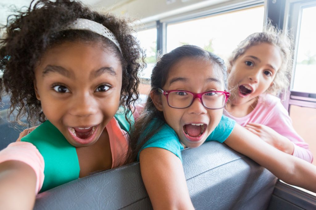 Diverse elementary schoolgirls make faces while riding to school on a school bus.