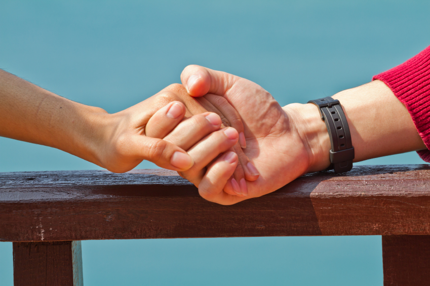 Man and woman hands touch in gentle, soft way on blue sunny sky.