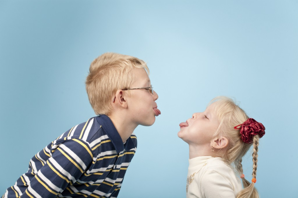 boy and girl stick out tongues to each other