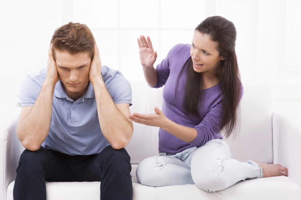 Are you with me? Furious young woman shouting and gesturing while man sitting close to her on the couch and holding head in hands