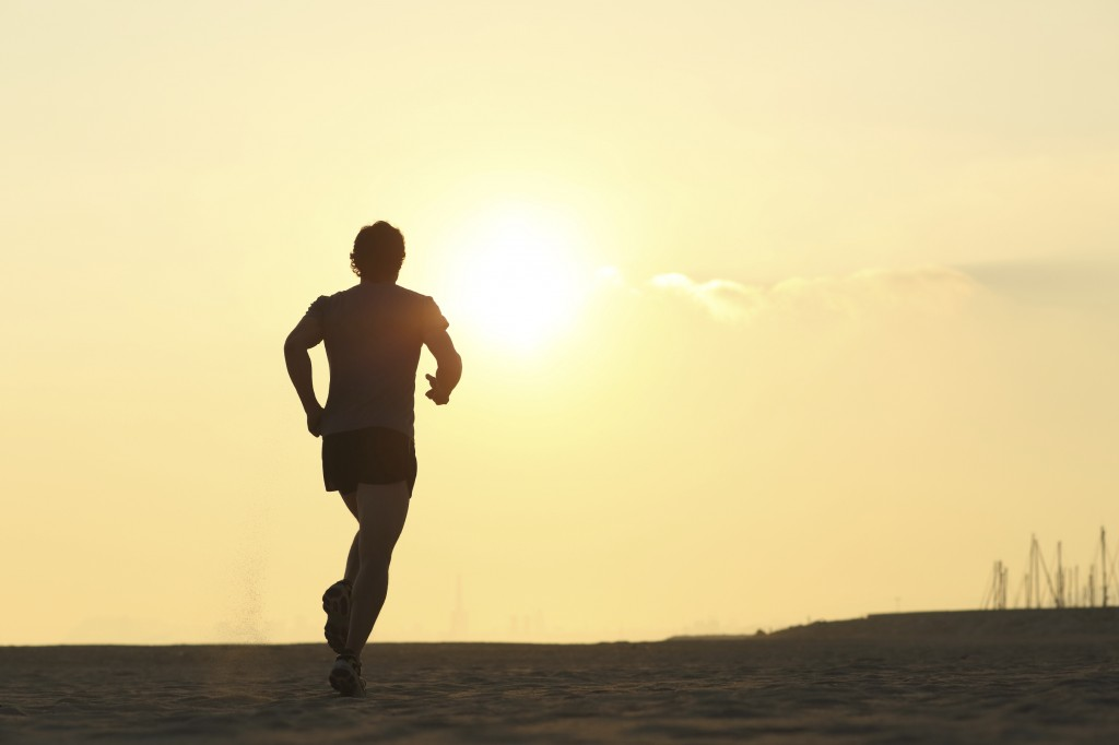 Backlight of a jogger running on the beach with the sun beside