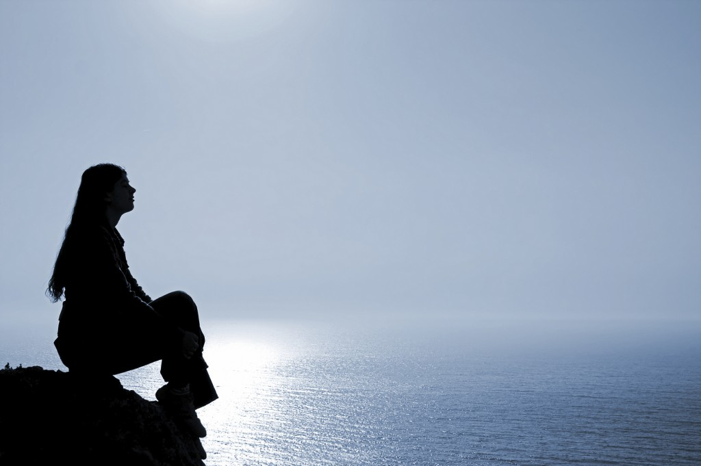 silhouette of woman against the ocean