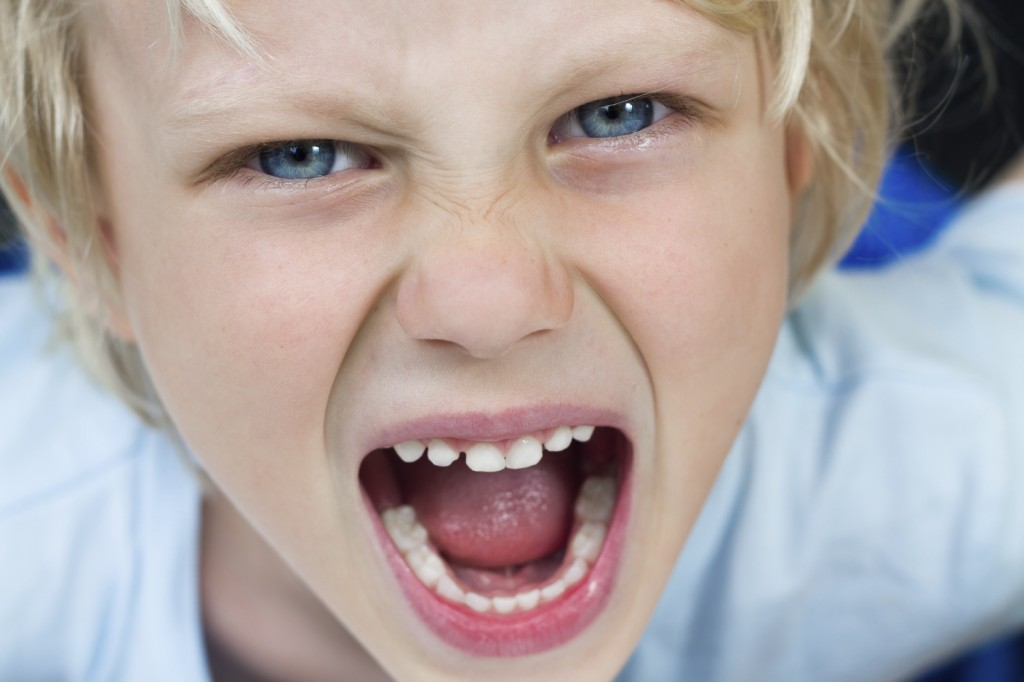 close-up portrait of a very angry screaming boy
