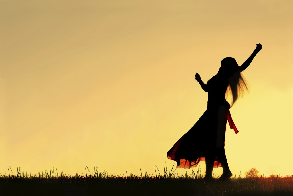 A woman wearing a long skirt, with long blonde hair, is dancing and spinning, while silhouetted against the evening sky