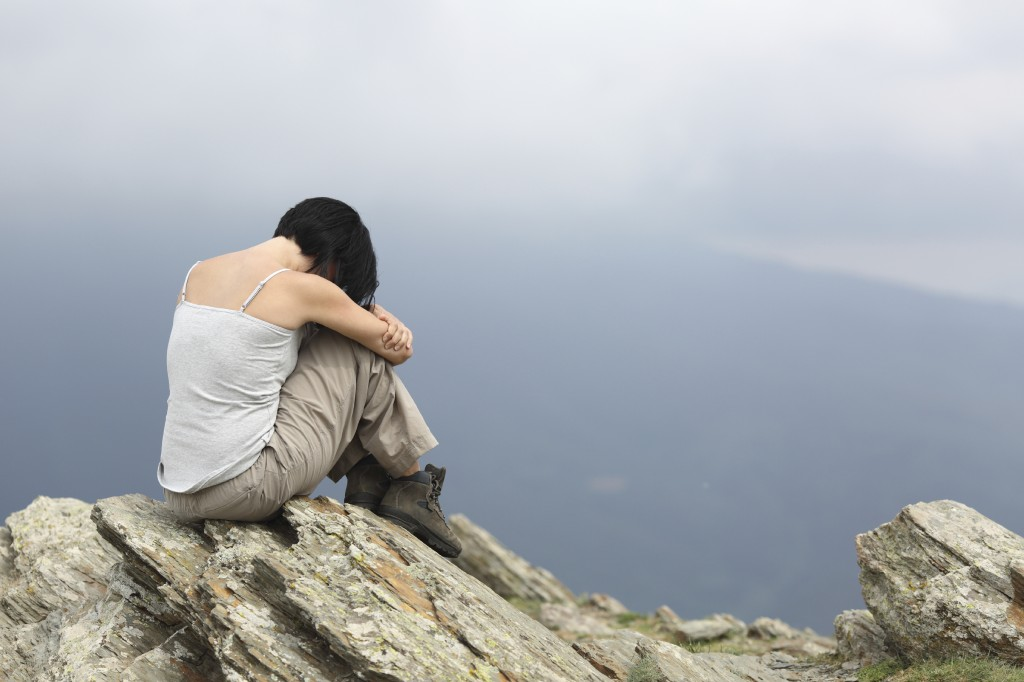 Depressed and sad woman alone in the mountain