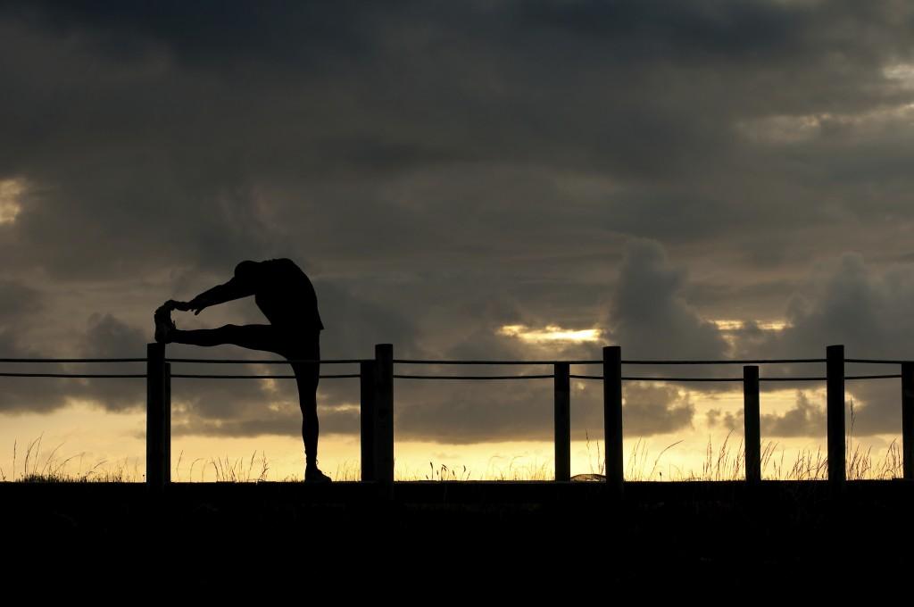 athlete stretching at dusk