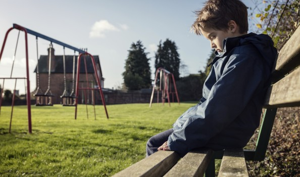 Lonely child sitting on play park playground bench