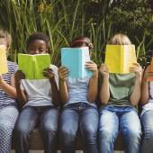 Children reading books at park