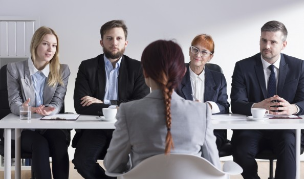 Woman during job interview and four businesspeople sitting by office table