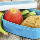 Healthy lunch box consisting cheese roll, red apple and banana