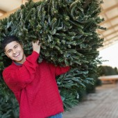 Happy man carrying Christmas tree to car after purchasing