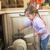 Smiling caucasian girl helping in  kitchen taking plates out of