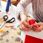 Senior women sews by hand