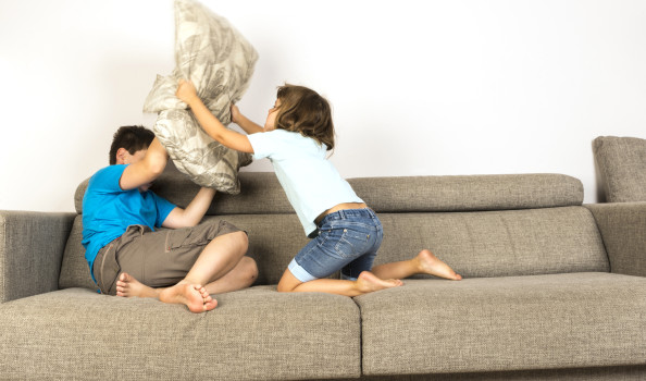 Children fighting together with pillows