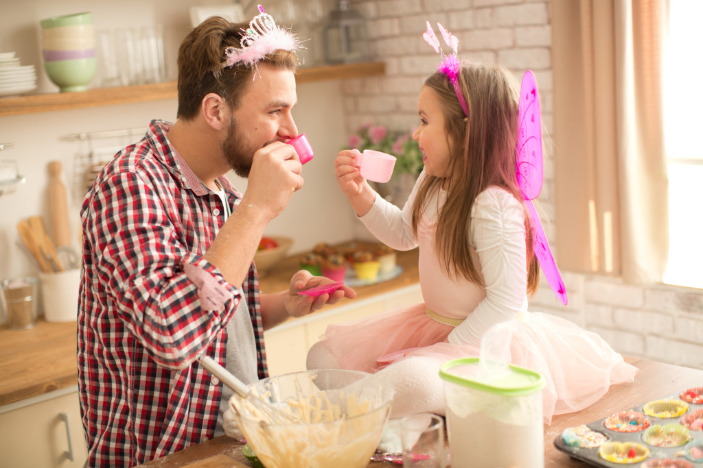 Father and daughter baking and having tea party in kitchen.