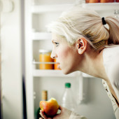 Young woman with apple in hand in front of fridge