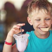 Little boy eating ice cream at restaurant