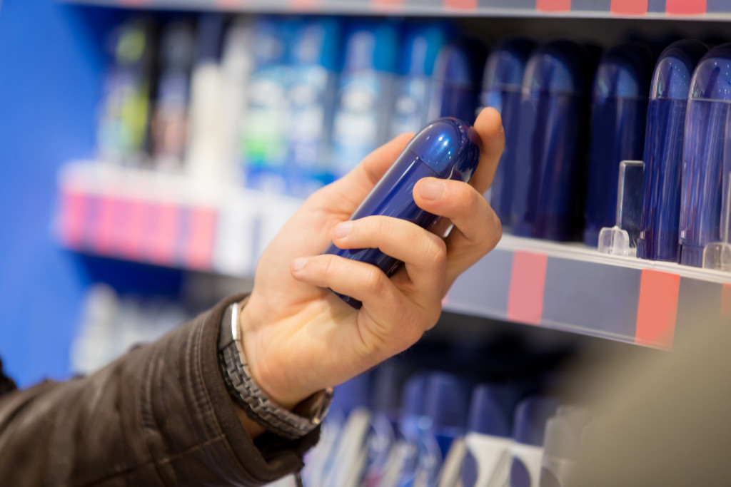 Man choosing cosmetics in supermarket