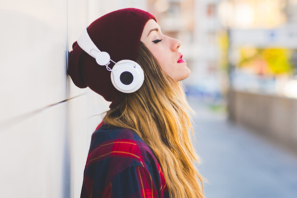 Girl with a beanie on wearing headphones up against a wall