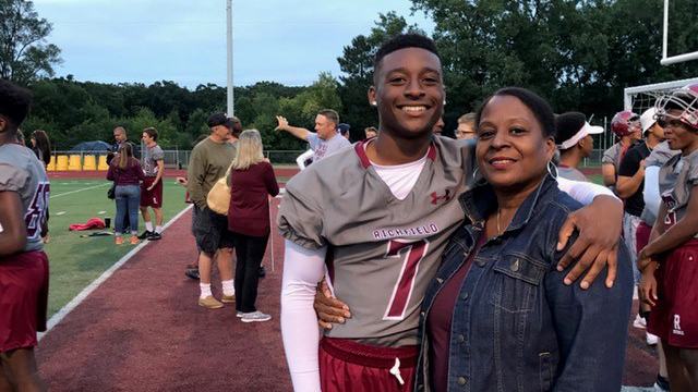 Smiling high school football player standing with his mom
