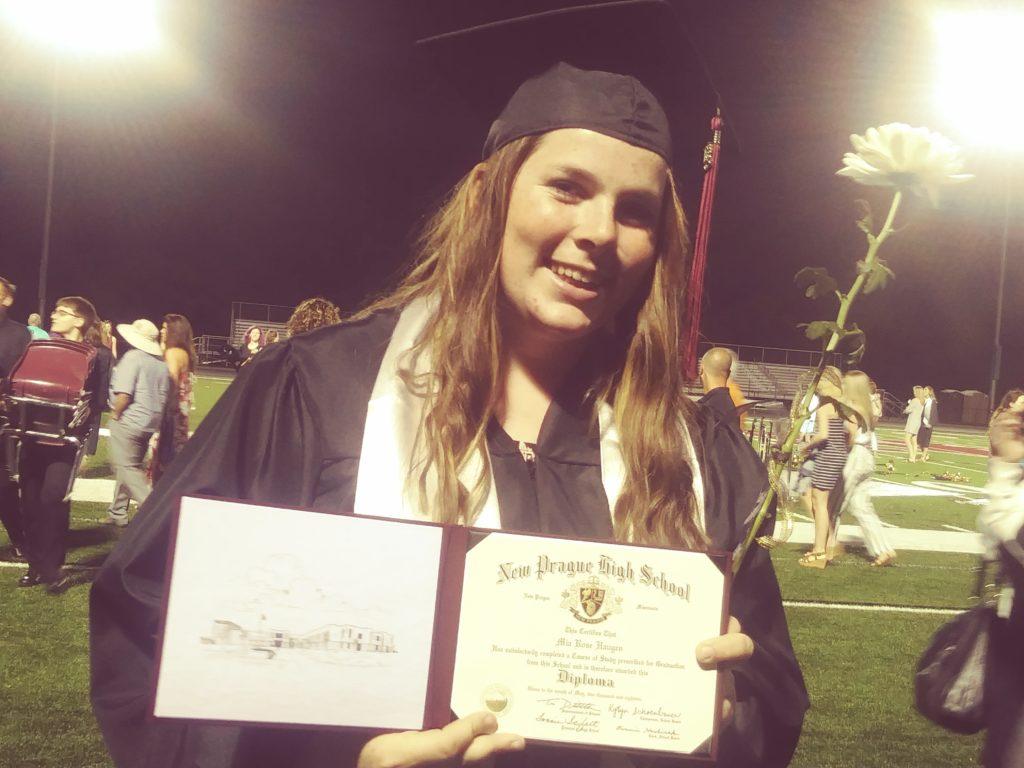 Smiling high school graduate female on a football field