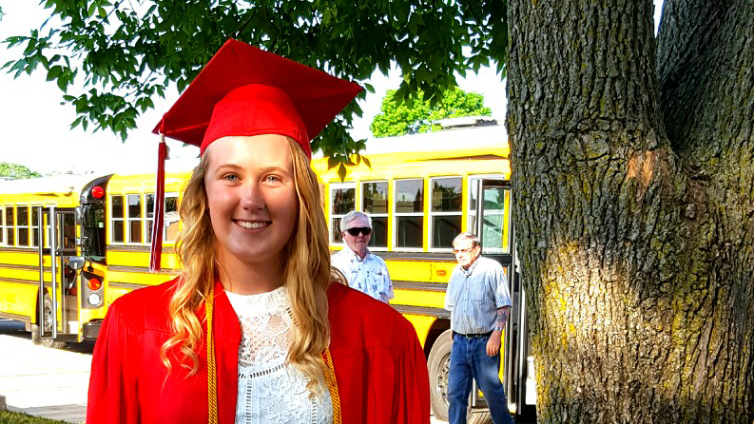 Smiling high school female graduate in red cap and gown, standing in front of school buses