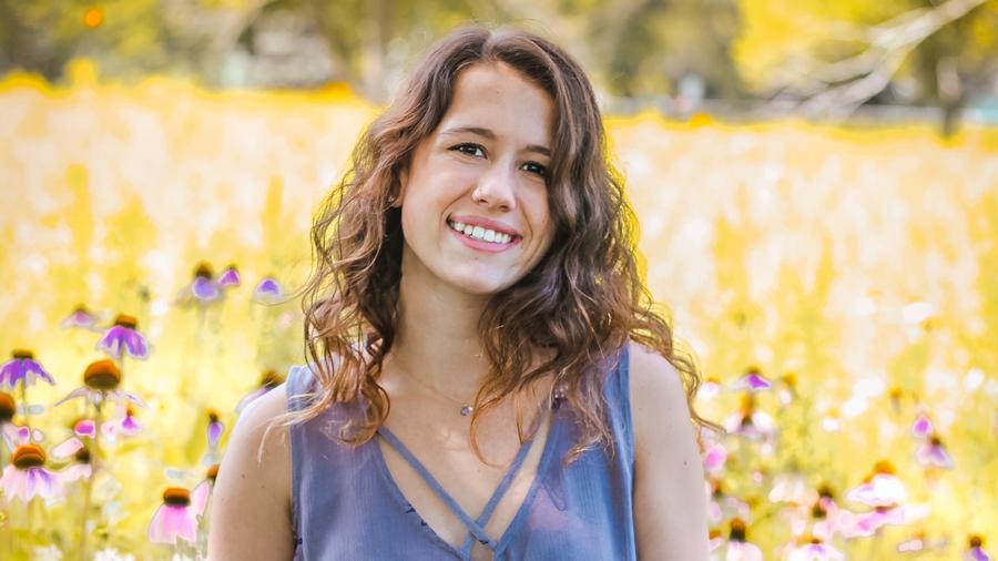 Smiling teenage girl in field of flowers