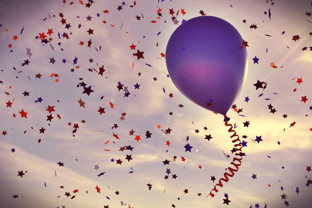 A solitary purple balloon on a vintage looking sky, with many confetti stars falling down.