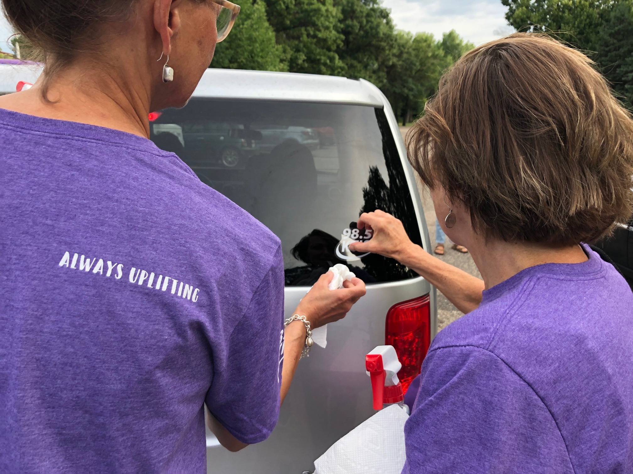 two females putting window stickers on a car