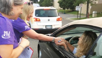 two women handing out bumper stickers to a lady in a car