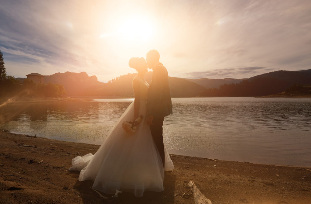 silhouette of bride and groom embracing near lake, enjoying their special moment and feeling in love.