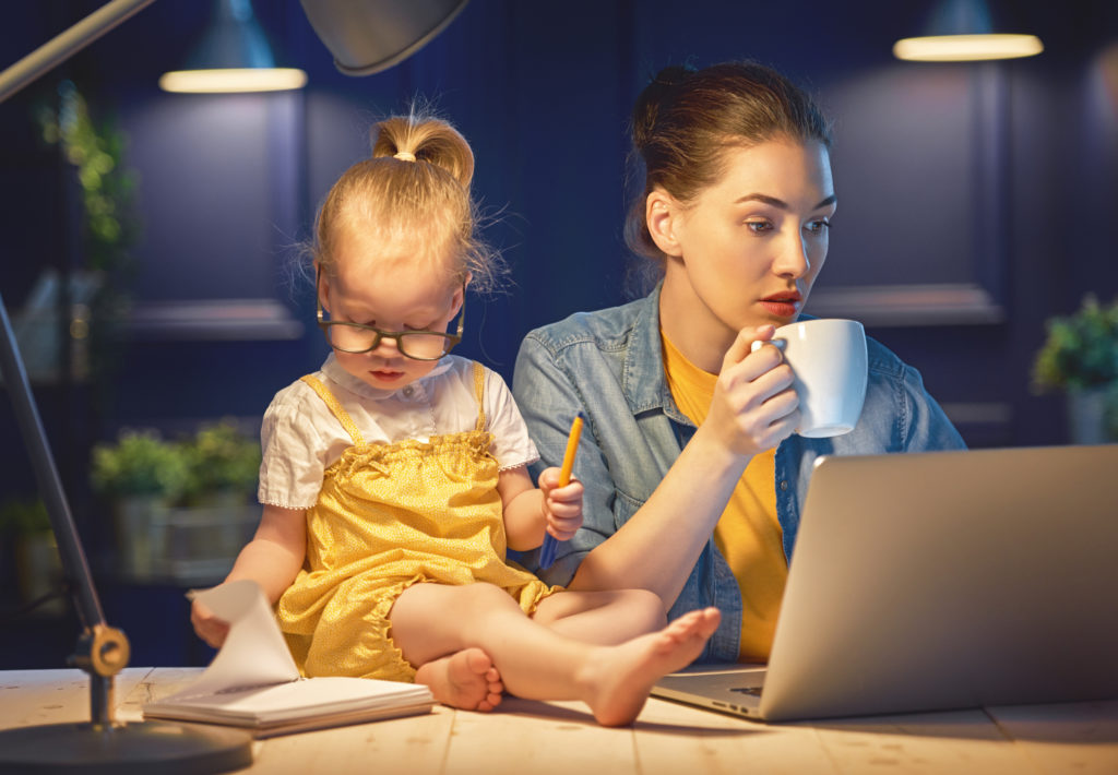 Young mother with toddler child working on the computer from home at night.