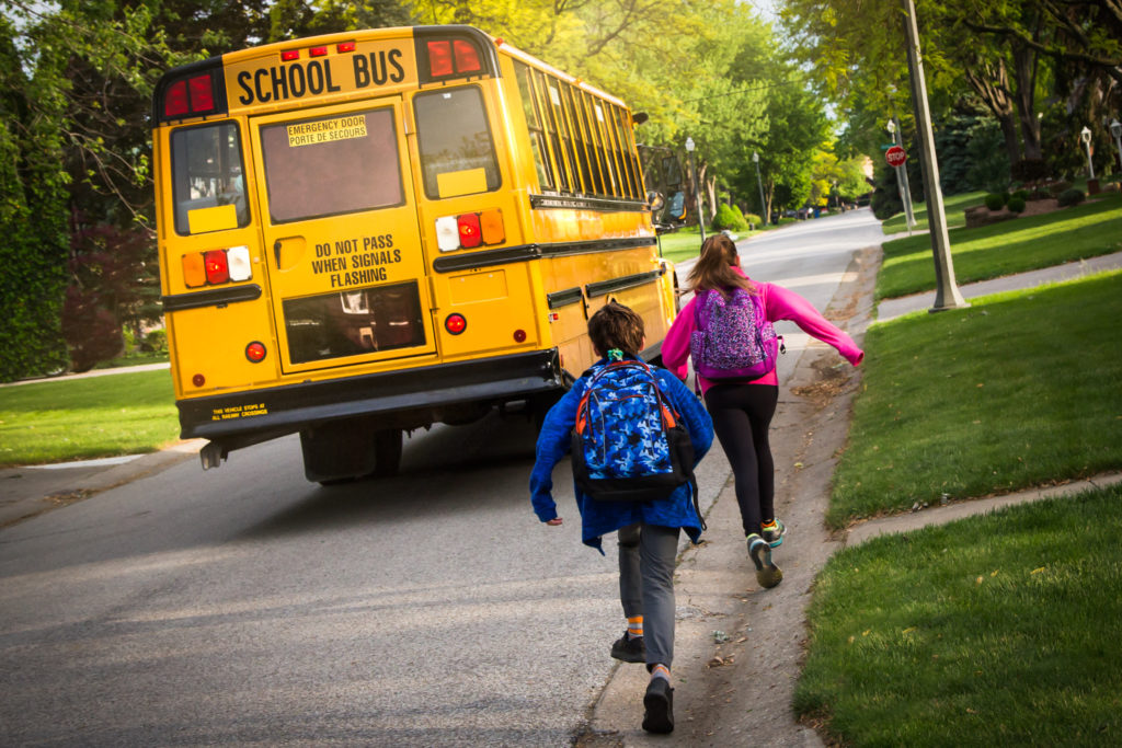 Two elementary students run to catch the school bus in the morning.