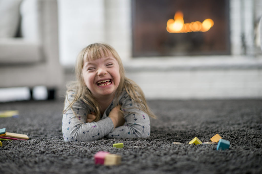 An elementary-age girl with Down Syndrome is in her living room. She is laying on the carpet and smiling happily. Toys are scattered around her.