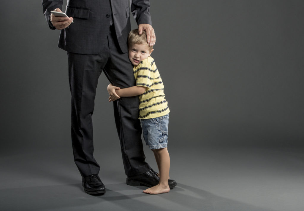 An adorable young boy clings to his father's leg. The Father is dressed in a business suit and he is looking at his smart phone.