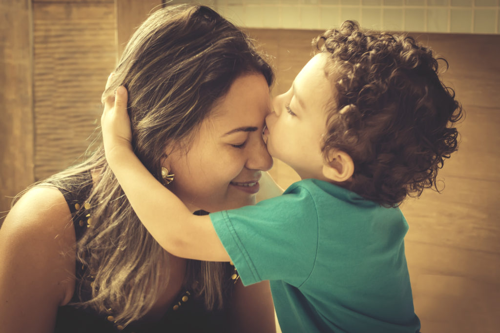 Little 2 year old boy, hugging and kissing his mother, with affectionate gesture.