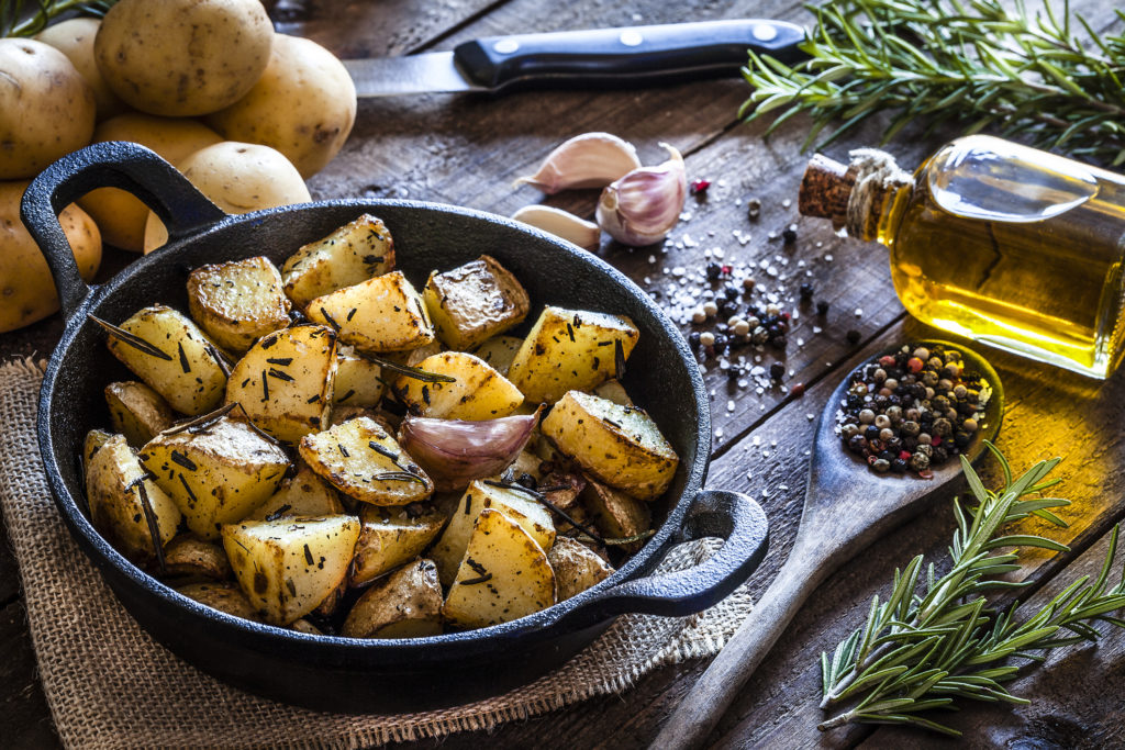 Cast iron pan filled with roasted potatoes shot on rustic wooden table. The cooking pan is at the left of an horizontal frame and the ingredients for cooking the potatoes are all around the pan placed directly on the table. The ingredients includes are raw potatoes, rosemary, olive oil, salt, pepper and garlic. Predominant colors are brown and yellow. DSRL studio photo taken with Canon EOS 5D Mk II and Canon EF 100mm f/2.8L Macro IS USM