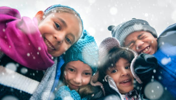 Smiling children outside on a snowy day