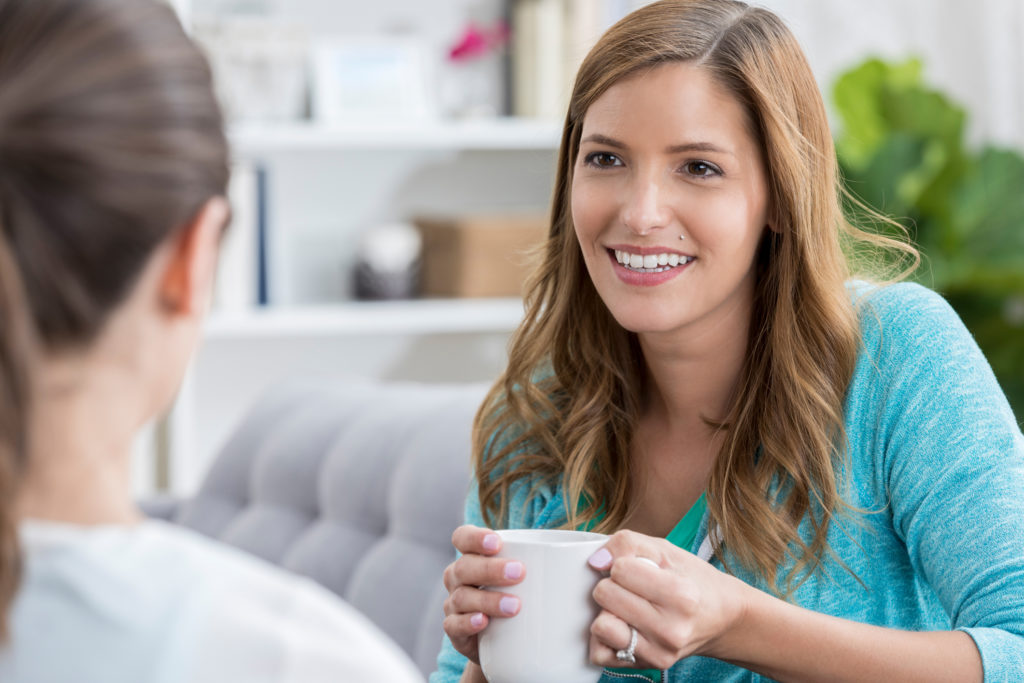 Attentive mid adult woman listens while her friend talks about something. The woman is drinking a cup of coffee.