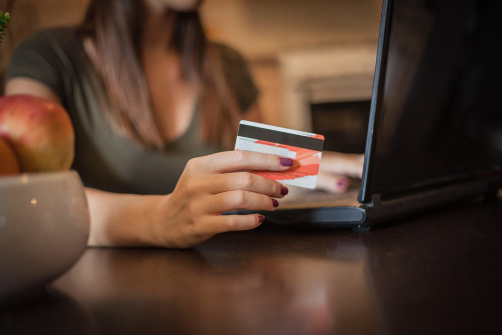 Close up of a woman shopping online with her credit card.
