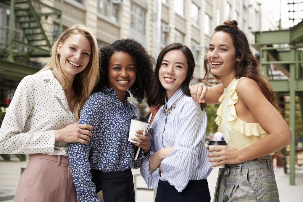 Four female coworkers smiling to camera outside