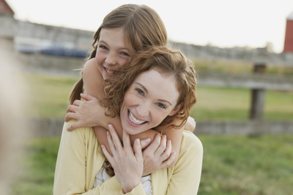 Mother and daughter hugging outdoors.