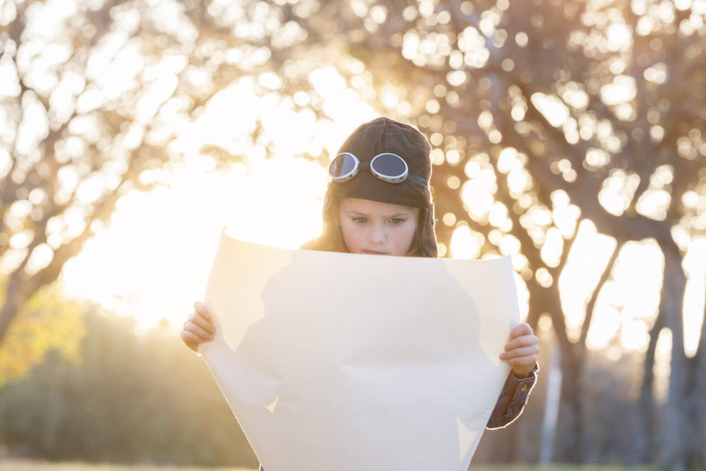 Elementary age girl is playing outdoors while wearing an old fashioned pilot costume and reading a large paper map.