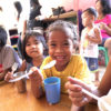 a group of impoverished children eating at a table