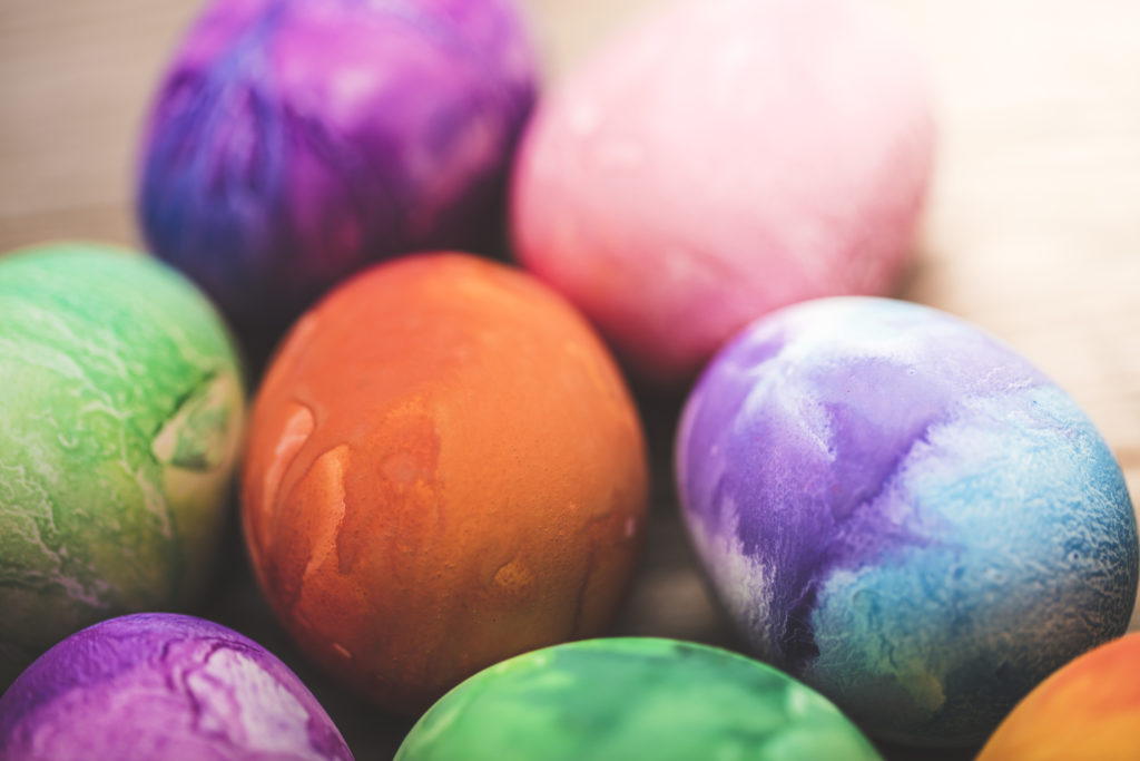 A stock photo of Dyed Easter eggs on a wood background.