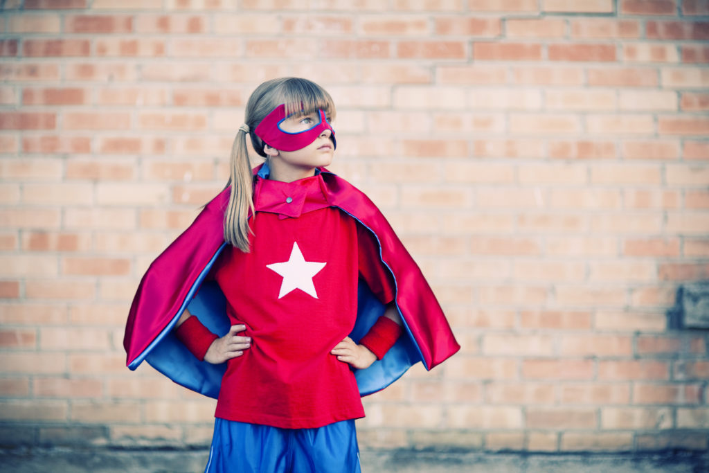 Portrait of a little girl superhero. She is ready for the challenge.