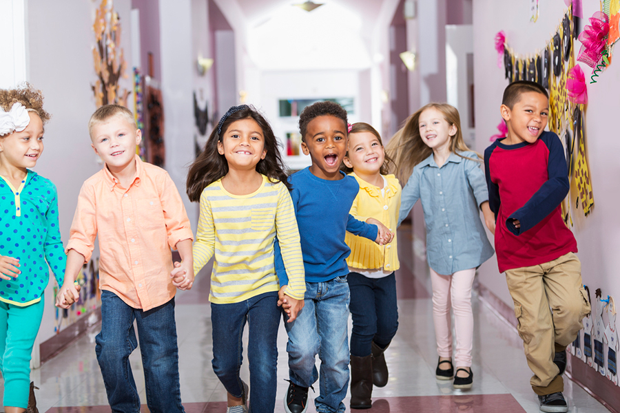 A group of multi-racial kids running down a hallway