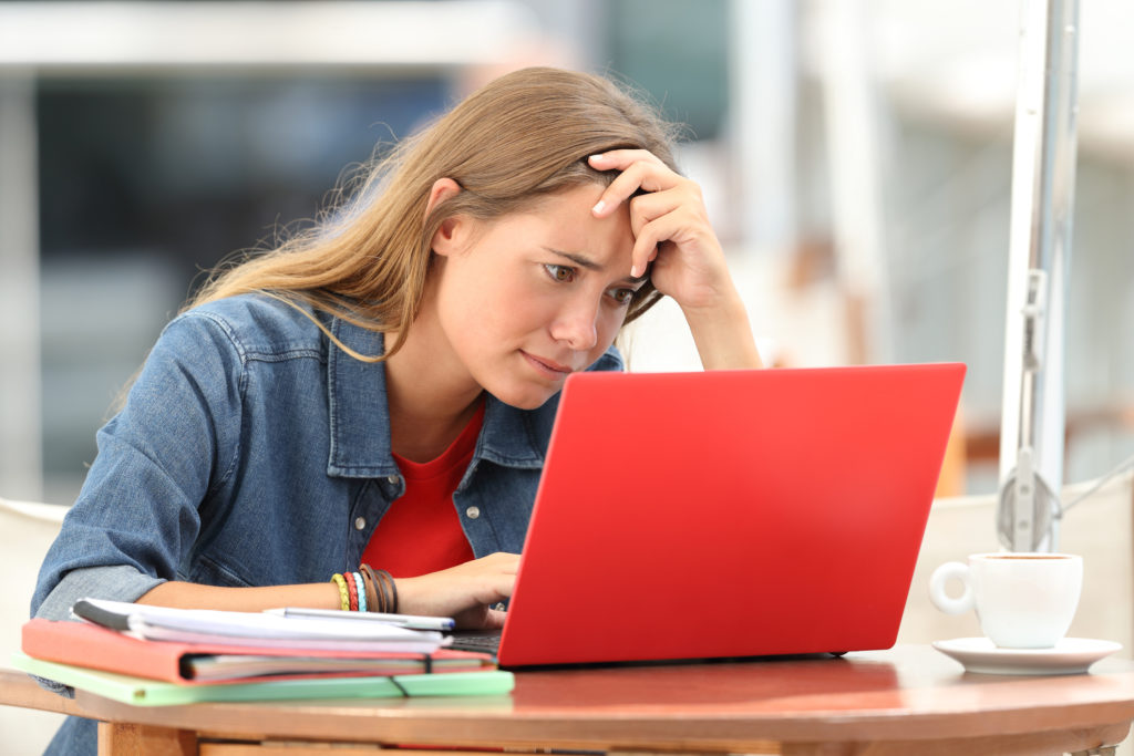 worried looking female student looking at a computer