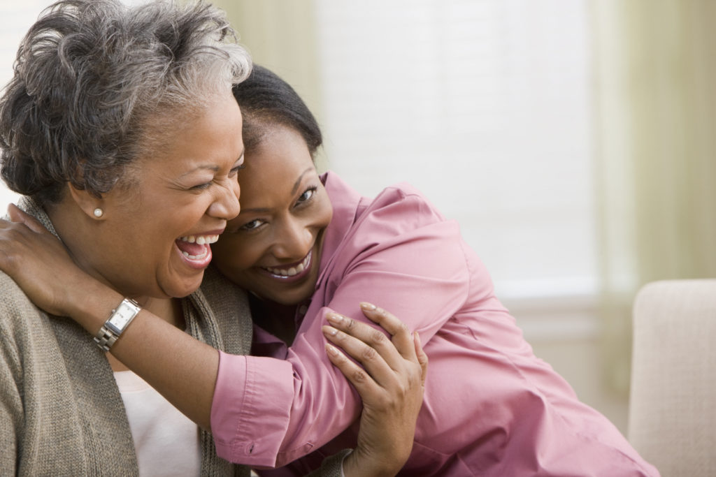 An African-American woman hugging her mom