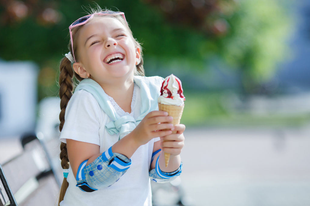 Cheerful little girl in the Park with ice cream cone